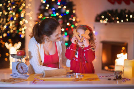 Mother and little girl baking Christmas pastry. Children bake gingerbread. Toddler child preparing cookie for family dinner on Xmas eve. Decorated kitchen or dining room with fireplace, tree, candles. Stock Photo