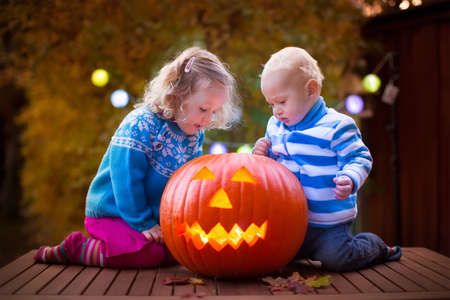 trick or treating: Little girl and boy carving pumpkin at Halloween. Dressed up children trick or treating. Kids trick or treat. Child in witch costume playing in autumn park. Toddler kid with jack-o-lantern.