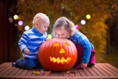 Meisje en jongen carving pompoen op Halloween. Verklede kinderen truc of behandelen. Kinderen trick or treat. Kind in heks kostuum spelen in de herfst park. Peuter jongen met jack-o-lantern.