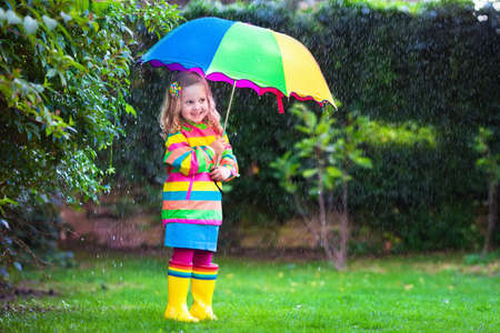 toddler walking: Little girl with colorful umbrella playing in the rain. Kids play outdoors by rainy weather in fall. Autumn fun for children. Toddler kid in raincoat and boots walking in the garden. Summer shower.