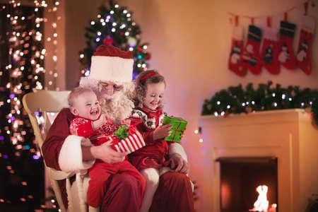 niños ayudando: Santa Claus y los niños que abren presentes en la chimenea. Los niños y el padre en el traje de Santa y barba abierta regalos de Navidad. Niña que ayuda con el actual saco. Familia bajo el árbol de Navidad en la chimenea. Foto de archivo