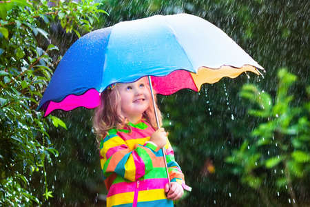 rain: Little girl with colorful umbrella playing in the rain. Kids play outdoors by rainy weather in fall. Autumn fun for children. Toddler kid in raincoat and boots walking in the garden. Summer shower.