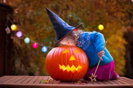 frutas divertidas: Niña y niño talla de calabaza en Halloween. Vestida niños truco o trato. Trick or treat Kids. Niño en el traje de juego bruja en el Parque de otoño. Niño del niño con jack-o-lantern. Foto de archivo