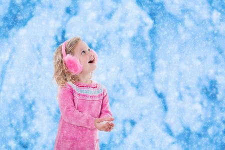 neige qui tombe: Petite fille en rose pull en tricot et de fourrure Earwarmer attraper les flocons de neige dans le parc d'hiver. Les enfants jouent en plein air dans la for�t enneig�e. Les enfants attrapent des flocons de neige. Enfant en bas �ge jouer � l'ext�rieur dans une temp�te de neige.
