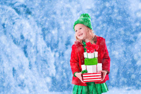 green clothes: Little girl in red and green knitted hat holding Christmas present boxes in winter park on Xmas eve. Kids play outdoor in snowy winter forest. Children opening presents. Toddler kid playing with gifts Stock Photo