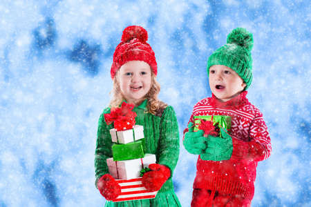 boy kid: Little girl and boy in red and green knitted hat holding Christmas present boxes in winter park on Xmas eve. Kids play outdoor in snowy winter forest. Children opening presents. Toddler kid with gifts