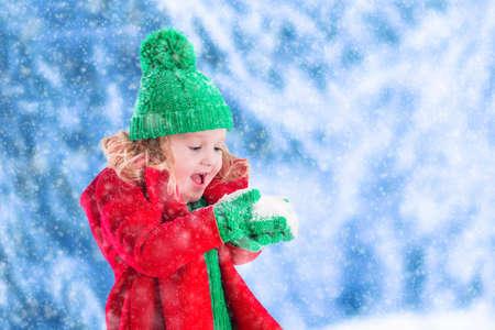 Bambina in giacca rossa e maglia cappello gustare fiocchi di neve verdi nel parco d'inverno alla vigilia di Natale. I bambini giocano all'aperto nevoso inverno foresta. I bambini catturano fiocchi di neve a Natale. Bambino Bambino che gioca.