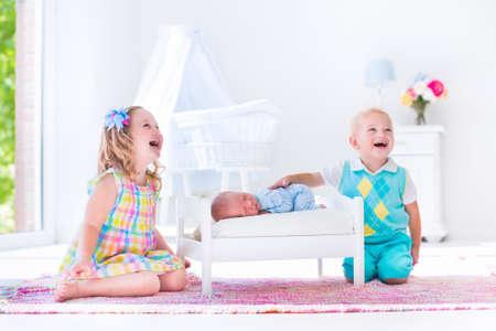 nato: Bambini che giocano con il bambino appena nato. Fratellino Bambino e prescolare ragazza giocano con nuovo ragazzo nato a letto giocattolo. Interno della scuola materna e biancheria da letto tessile. I bambini incontrano fratello infantile. Camera da letto bianco con culla.