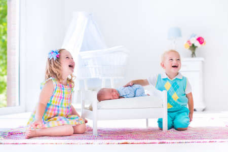 sister: Kids playing with newborn baby brother. Toddler and preschooler girl play with new born boy in toy bed. Nursery interior and textile bedding. Children meet infant sibling. White bedroom with bassinet.