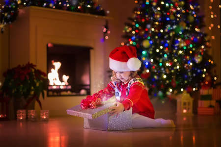 Family on Christmas eve at fireplace. Kids opening Xmas presents. Children under Christmas tree with gift boxes. Decorated living room with traditional fire place. Cozy warm winter evening at home. Stock Photo