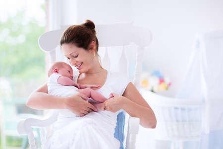 senos: Joven madre sosteniendo a su hijo recién nacido. Bebé lactante mamá. La mujer y el muchacho recién nacido se relajan en una habitación blanca con mecedora y azul cuna. Vivero interior. Madre bebé la lactancia materna. Familia en el país