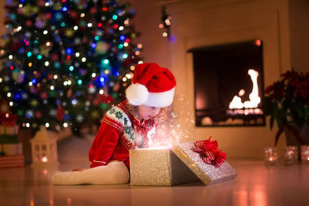 decorated christmas tree: Family on Christmas eve at fireplace. Kids opening Xmas presents. Children under Christmas tree with gift boxes. Decorated living room with traditional fire place. Cozy warm winter evening at home. Stock Photo
