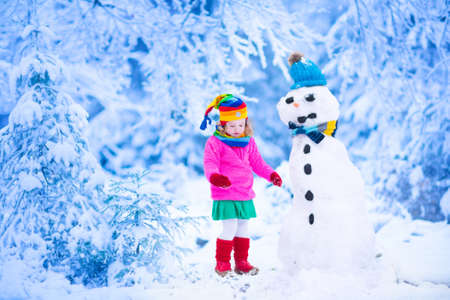 having fun in winter time: Funny little toddler girl in a red knitted Nordic hat and warm coat playing with a snow. Kids play outdoors in winter. Children having fun at Christmas time. Child building snowman at Xmas.