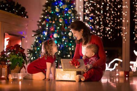 Familie op kerstavond bij open haard. Moeder en kleine kinderen opening Xmas presenteert. Kinderen met geschenkdozen. Woonkamer met traditionele open haard en versierde boom. Gezellige winter avond thuis. Stockfoto