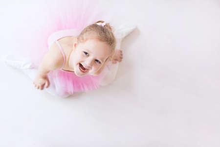 prinzessin: Kleine Ballerina Mädchen in einem rosa Tutu. Nettes Kind tanzt klassisches Ballett in weiß Studio. Kinder tanzen. Junge Tänzer in einer Klasse. Vorschulkind sitzt auf Holzboden. Kopieren Sie Platz für Ihren Text.