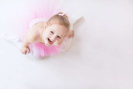 Little ballerina girl in a pink tutu. Cute child dancing classical ballet in white studio. Children dance. Young dancer in a class. Preschool kid sitting on hardwood floor. Copy space for your text. Stock Photo