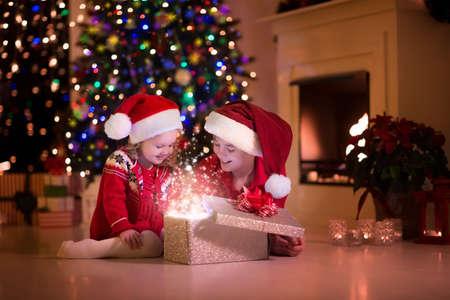 Familie op kerstavond bij open haard. Kinderen openen Xmas presenteert. Kinderen onder de kerstboom met geschenkdozen. Ingerichte woonkamer met traditionele open haard. Gezellige warme winter 's avonds thuis.