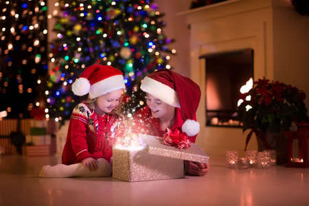 Family on Christmas eve at fireplace. Kids opening Xmas presents. Children under Christmas tree with gift boxes. Decorated living room with traditional fire place. Cozy warm winter evening at home. Banque d'images