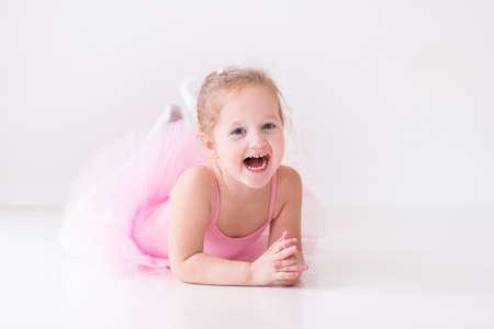 乳幼児: ピンクのチュチュのバレリーナ少女。ホワイト スタジオでクラシック バレエを踊る愛らしい子です。子供たちをダンスします。子供を実行します。若い才能のあ