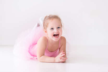 Little ballerina girl in a pink tutu. Adorable child dancing classical ballet in a white studio. Children dance. Kids performing. Young gifted dancer in a class. Preschool kid taking art lessons. Stock Photo - 45219761
