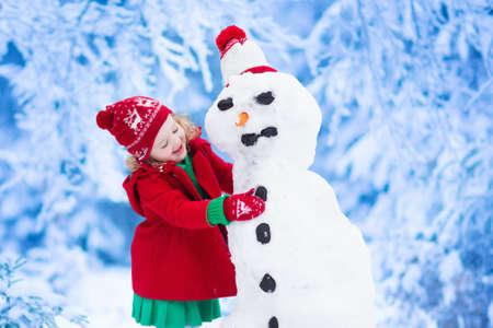 Funny little toddler Dziewczynka w czerwonym kapeluszu i nordic dzianiny ciepły płaszcz grając w śniegu. Dzieci grają na zewnątrz w zimie. Dzieci zabawy w czasie świąt. Dziecko na Boże Narodzenie bałwan budynku. Zdjęcie Seryjne