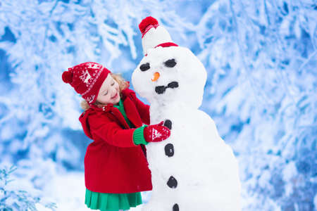 child: Funny little toddler girl in a red knitted Nordic hat and warm coat playing with a snow. Kids play outdoors in winter. Children having fun at Christmas time. Child building snowman at Xmas.