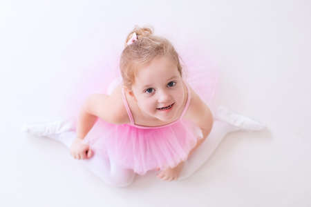 pointe: Little ballerina girl in a pink tutu. Adorable child dancing classical ballet in a white studio. Children dance. Kids performing. Young gifted dancer in a class. Preschool kid taking art lessons.