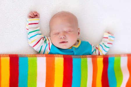 bebes ni�as: Beb� reci�n nacido en la cama. Ni�o reci�n nacido durmiendo bajo una manta colorida. Duermen los ni�os. Ropa de cama para los ni�os. Siesta infantil en la cama. Ni�o sano poco despu�s del nacimiento. Ropa para ni�os. Foto de archivo