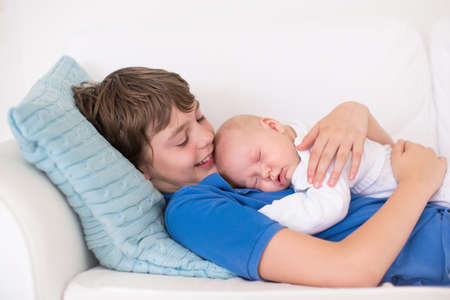 family sofa: Happy laughing boy holding his sleeping newborn baby brother. Siblings with big age difference. Children playing at home on a white couch. New born child taking a nap. Kids bonding. Family love.
