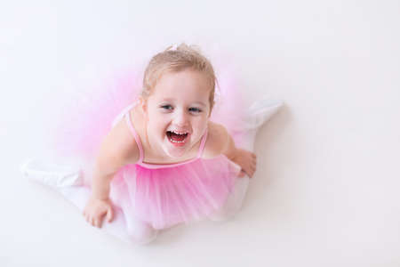 ballerina costume: Little ballerina girl in a pink tutu. Adorable child dancing classical ballet in a white studio. Children dance. Kids performing. Young gifted dancer in a class. Preschool kid taking art lessons.