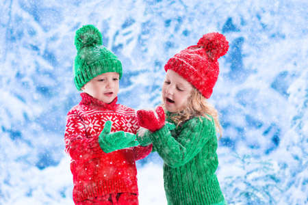 jungle boy: Little girl and boy in red and green knitted hat catching snowflakes in winter park on Christmas eve. Kids play outdoor in snowy winter forest. Children catch snow flakes on Xmas. Toddler kid playing.