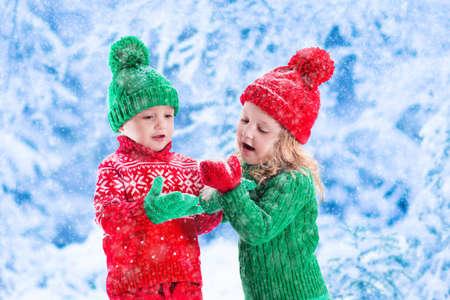 gemelos ni�o y ni�a: Ni�a y ni�o en los copos de nieve del sombrero captura de punto rojo y verde en el Parque de invierno en la v�spera de Navidad. Los ni�os juegan al aire libre en el bosque de invierno cubierto de nieve. Los ni�os cogen copos de nieve en Navidad. Chico de juego del ni�o.