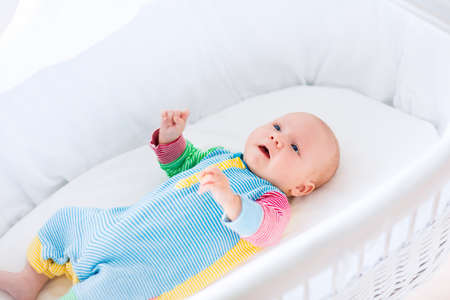 bassinet: Newborn baby boy playing in bed on a sunny morning. New born child relaxing in bassinet. Children sleep. Bedding and clothing for kids. Infant napping in bed. Healthy little kid shortly after birth.