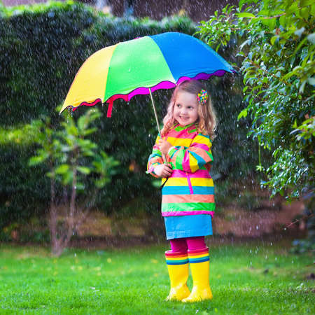 raining: Little girl with colorful umbrella playing in the rain. Kids play outdoors by rainy weather in fall. Autumn fun for children. Toddler kid in raincoat and boots walking in the garden. Summer shower.