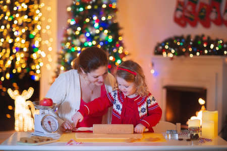fireplace family: Mother and little girl baking Christmas pastry. Children bake gingerbread. Toddler child preparing cookie for family dinner on Xmas eve. Decorated kitchen or dining room with fireplace, tree, candles. Stock Photo