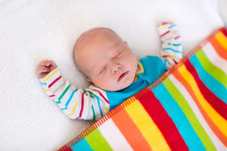 Newborn baby boy in bed. New born child sleeping under a colorful blanket. Children sleep. Bedding for kids. Infant napping in bed. Healthy little kid shortly after birth. Clothing for kids.