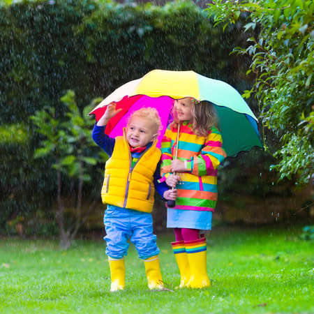 Little girl and boy with colorful umbrella playing in the rain. Kids play outdoor by rainy weather in fall. Autumn fun for children. Toddler kid in raincoat and boots walk in the garden. Summer shower