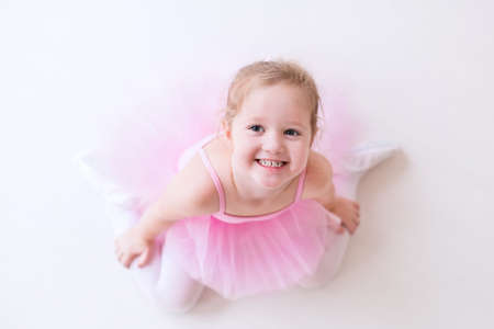 early childhood: Little ballerina girl in a pink tutu. Adorable child dancing classical ballet in a white studio. Children dance. Kids performing. Young gifted dancer in a class. Preschool kid taking art lessons.