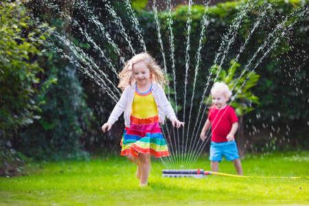 Kind spelen met tuin sprinkler. Kleuter jongen rennen en springen. Zomer buiten waterpret in de achtertuin. Kinderen spelen met slang water geven bloemen. Kinderen lopen en spatten op warme zonnige dag. Stockfoto