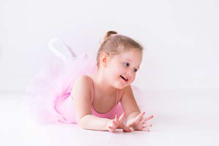 petite fille avec robe: Petite fille de ballerine dans un tutu rose. Adorable enfant danser le ballet classique dans un studio blanc. Des enfants dansent. Enfants ex�cution. Jeune danseuse de talent dans une classe. Enfant d'�ge pr�scolaire � prendre des le�ons d'art. Banque d'images