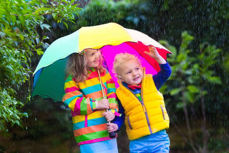 rain weather: Little girl and boy with colorful umbrella playing in the rain. Kids play outdoor by rainy weather in fall. Autumn fun for children. Toddler kid in raincoat and boots walk in the garden. Summer shower