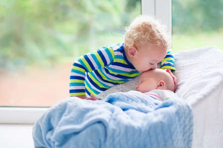 new age: Cute little boy kissing his newborn brother. Toddler kid meeting new born sibling. Infant sleeping in white bouncer under a blanket. Kids playing and bonding. Children with small age difference.