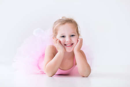 Bailarina de niña pequeña en un tutú rosado. Adorable niño bailando ballet clásico en un estudio de blanco. Los niños bailan. Niños realizando. Bailarina talentosa joven en una clase. Niño preescolar a tomar clases de arte.