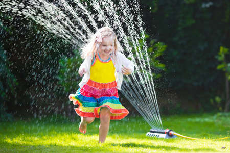 family gardening: Child playing with garden sprinkler. Preschooler kid running and jumping. Summer outdoor water fun in the backyard. Children play with hose watering flowers. Kids run and splash on hot sunny day.