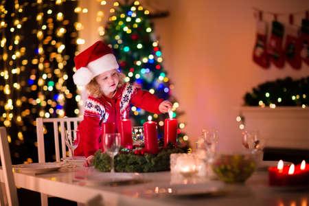 comida de navidad: La cena de Navidad en casa. Niño encendiendo una vela en la corona de adviento en la víspera de Navidad. Sala de estar decorada con chimenea y el árbol. Noche de invierno en la chimenea para una familia con niños. Niños celebrando.
