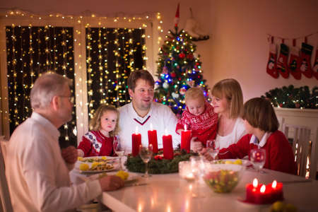 candle dinner: Big family with three children celebrating Christmas at home. Festive dinner at fireplace and Xmas tree. Parent and kids eating at fire place in decorated room. Child lighting advent wreath candle.