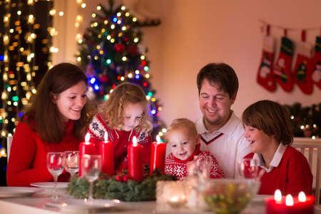 Grote familie met drie kinderen vieren Kerstmis thuis. Feestelijk diner in een open haard en Xmas boom. Ouder en kinderen eten bij haard in ingerichte kamer. Kind verlichting komst krans kaars. Stockfoto
