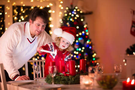 home lighting: Christmas dinner at home. Child lighting a candle on advent wreath on Xmas eve. Decorated living room with fireplace and tree. Winter evening at fire place for family with kids. Children celebrating.