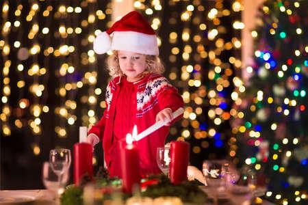 candela: Cena di Natale a casa. Bambino accendere una candela sulla corona di Avvento a vigilia di Natale. Decorato soggiorno con camino e albero. Sera d'inverno a camino per famiglie con bambini. I bambini che celebra.