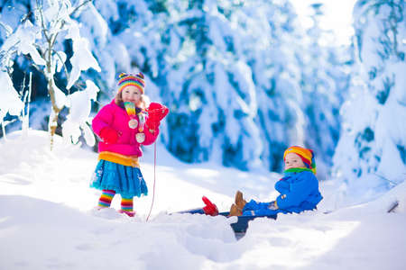 children at play: Little girl and baby boy enjoying a sleigh ride. Child sledding. Toddler kid riding a sledge. Children play outdoors in snow. Kids sled in snowy park. Outdoor winter fun for family Christmas vacation.
